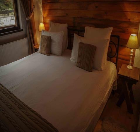 Cozy bed with pillows and rustic decor at Biovaleputna guest house